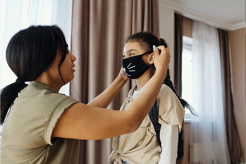 A lady putting a mask on a girl