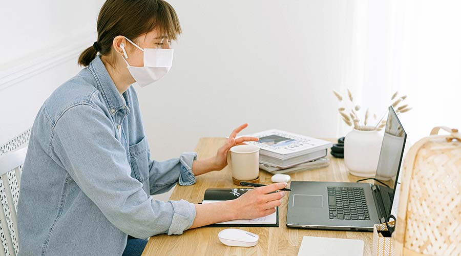 Woman in mask using laptop